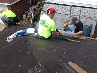 Durham School professor James Goedert (right) helps his team shingle the roof of a garage in north Omaha on Oct. 5.