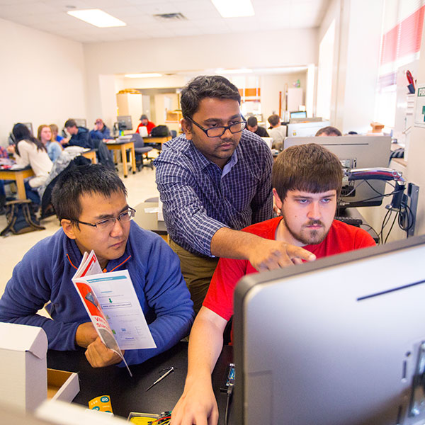 Santosh Pitla (center), assistant professor of biological systems engineering, assists students with a sensor-building project. Pitla is leading a new research project that will update techniques used to test tractors.