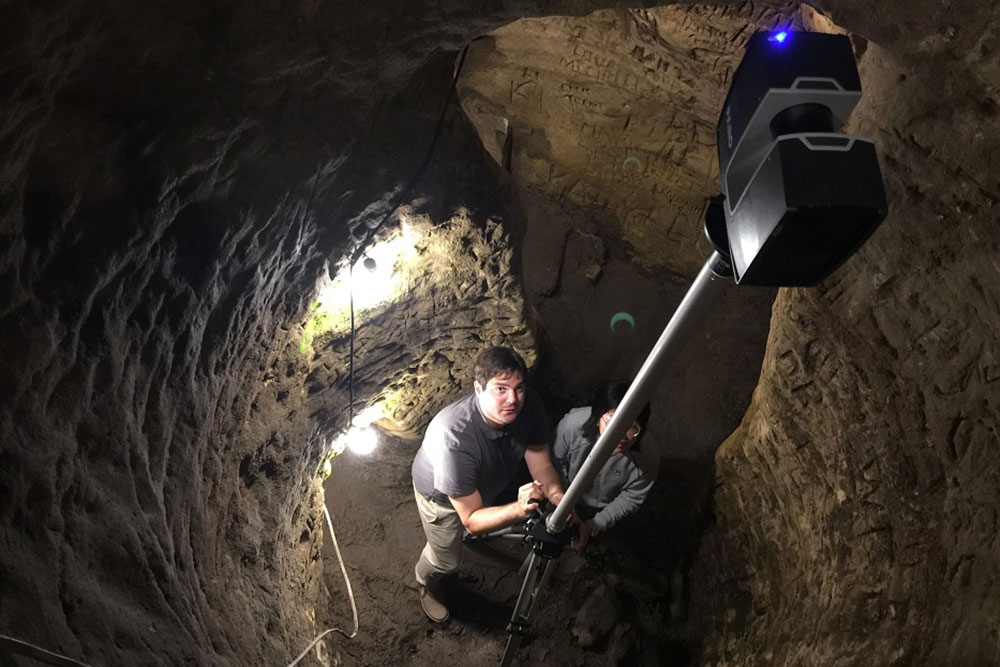 Richard Wood (left), assistant professor of civil and environmental engineering, and Ph.D. student Yijan Liao scan Robber's Cave using LiDAR. (Photo by History Nebraska)