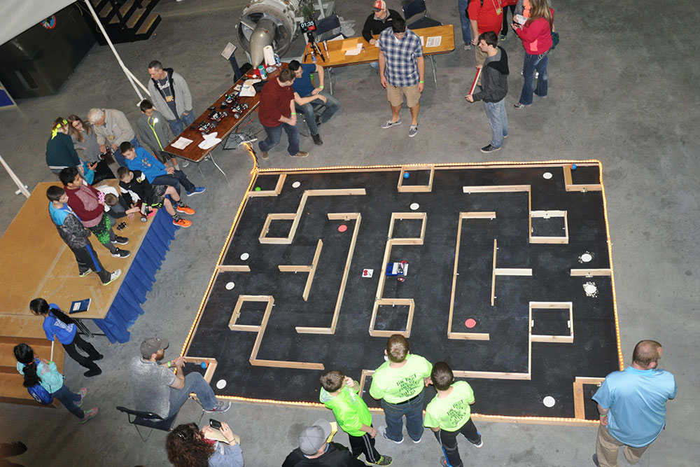 Students play a maze game by piloting a CEENBot robot through the course at the 2016 Nebraska Robotics Expo.