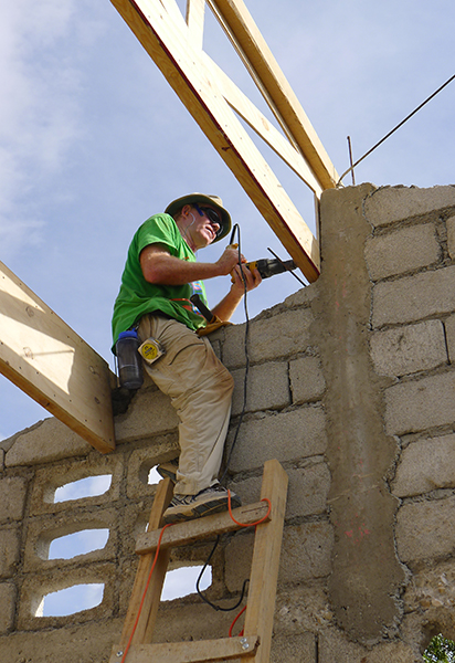 Durham professor James Goedert fastens one of the roof joists that were installed at the new Flower of Hope school.