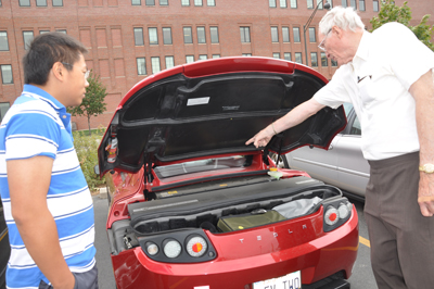 Electrical engineering graduate student Jay Cheng views the battery area of Professor Don Cox's Tesla Roadster in a UNL class on electrical vehicles.
