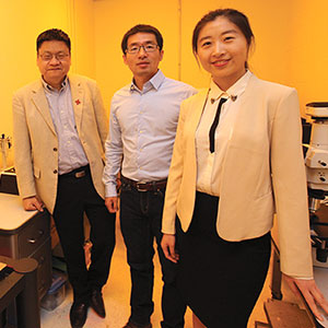 UNL engineers (from left) Yongfeng Lu, Lijia Jiang and Ying Liu stand in a laboratory illuminated by a special light that protects the lenses of the lab's scanning electron microscope. (Troy Fedderson / University Communications)
