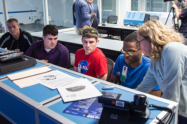 A NASA technician instructs UNL Air and Space Research team members on how to use Test Com equipment to communicate with divers during the testing session.