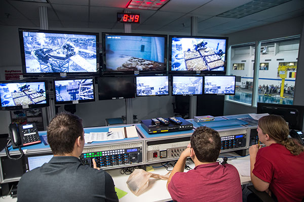UNL Air and Space Research team members watch the many monitors in Test Com mission control as divers test out their collection tool.