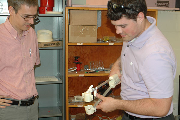 Faculty advisor Carl Nelson (left) and ASR project manager Luke Monhollon test a collection tool in a Scott Engineering Center laboratory.