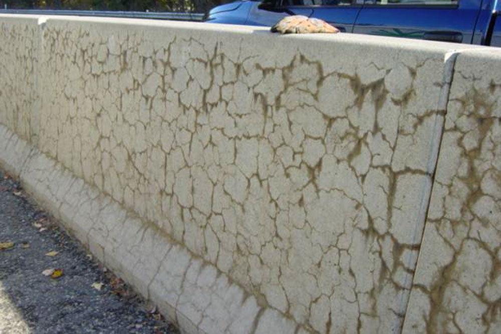 """Concrete structures affected by alkali-silica reaction (ARS) exhibit a """"turtle-back"""" pattern of cracks, as in this roadway median. These cracks can allow detrimental chemicals inside the concrete that can weaken other materials that are used to strengthen concrete."""