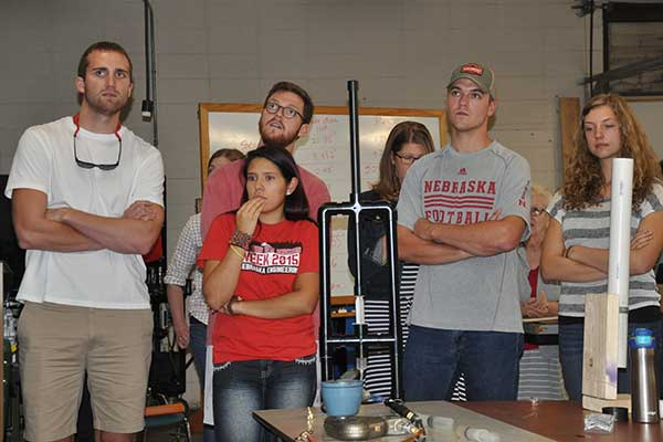 Christian Jewett, Mackenzie Miller, Kyle Olson, Kevan Reardon and Paula Sandoval watches as its device's performance is displayed on a screen at the Rapid Design Challenge.