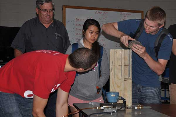 Micah Bolin, Sydney Gard and Ryan Hanousek prepare their device for the competition at the Rapid Design Challenge as Roger Hoy, professor of biological systems engineering, looks on.