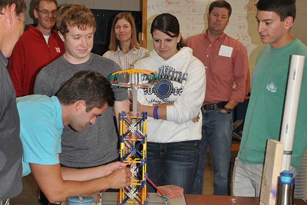 Zach Janecek attaches a tube to a syringe as teammates (from left) Michael Moeller, Kate Watts and Brinson Chapp watch at the Rapid Design Challenge.