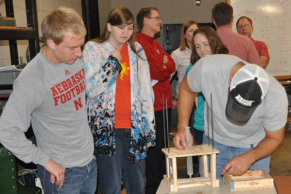 teammates Mitchell Maguire, Karissa Brehm and Julia Franck carefully observe while Justin Herting (right) makes and adjustment to the team's device during the Rapid Design Challenge.