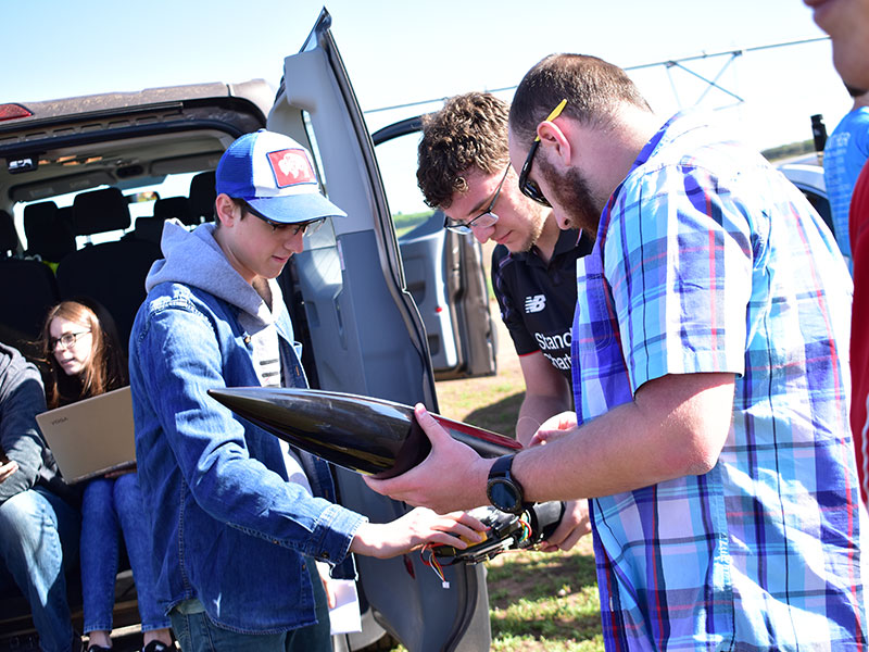 Members of the Husker Rocketry Team do a final inspection before take off.