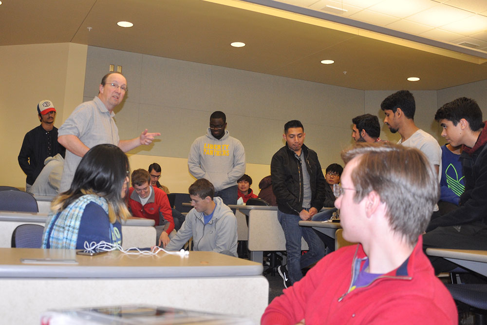 Mark Bauer, professor of practice in Electrical and Computer Engineering, instructs ELEC 121 students before they begin work on creating a device to shoot a rubber band from inside a three-sided box.