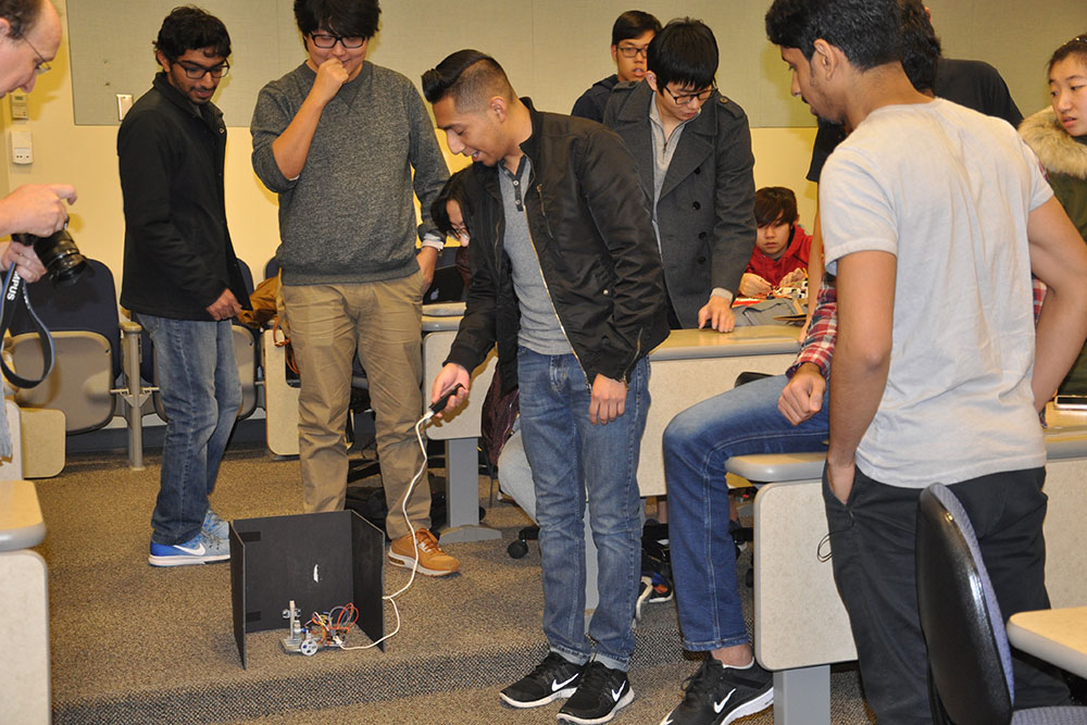 Students in ELEC 121 try to make a device they created shoot a rubber band from inside a three-sided box.