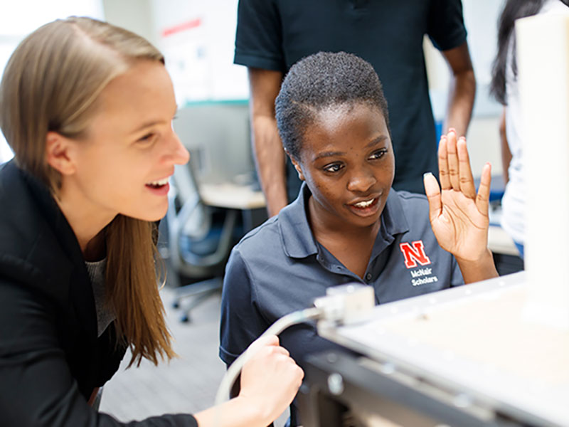 Christine Wittich and a student test a rubber model on the shake table.