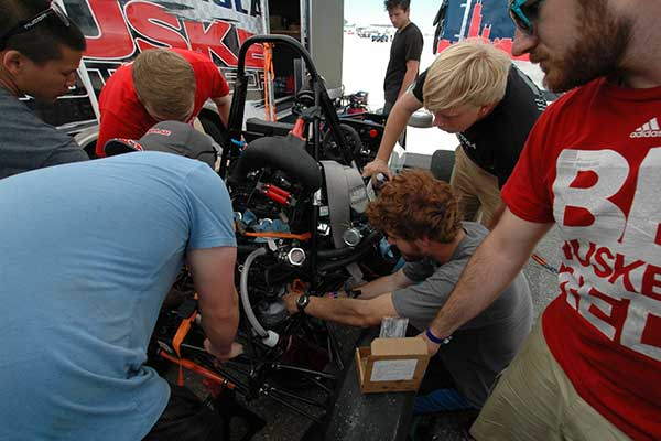 Husker Motorsports teammates work to repair the clutch on the car before Friday's autocross competition during the Formula SAE Lincoln event at Lincoln Airpark June 17-20.