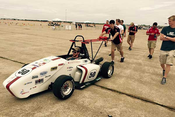 Husker Motorsports team members push the car to the track before a Thursday competition during the Formula SAE Lincoln event at Lincoln Airpark June 17-20.