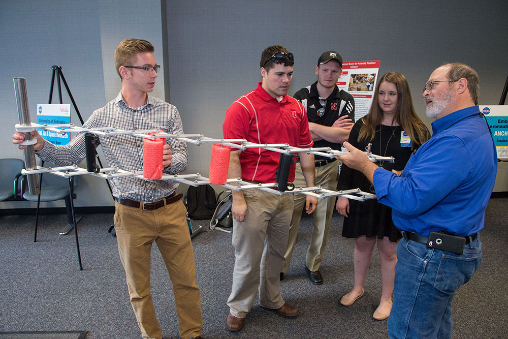 Members of the UNL Air and Space Research team show a NASA engineer how their gap spanner boom prototype works during the team presentation at the NASA Micro-g NExT Challenge at the Johnson Space Center in Houston.