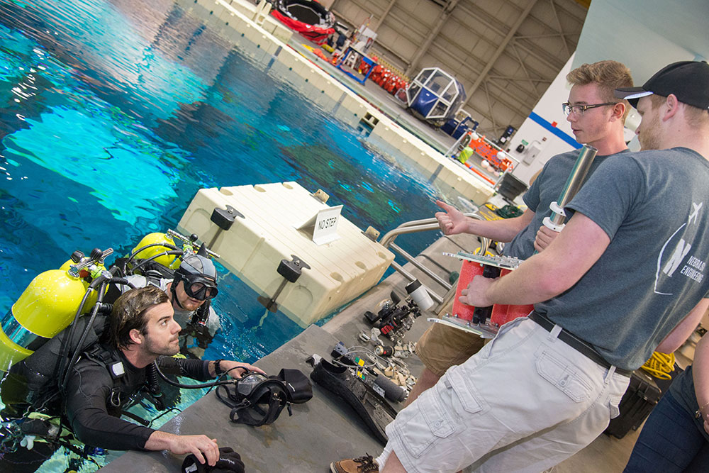 Nathan Borcyk and Brandon Jackson discuss how the gap spanner boom works with a diver who tested the prototype in June at the Neutral Buoyancy Laboratory's pool at the Johnson Space Center in Houston.