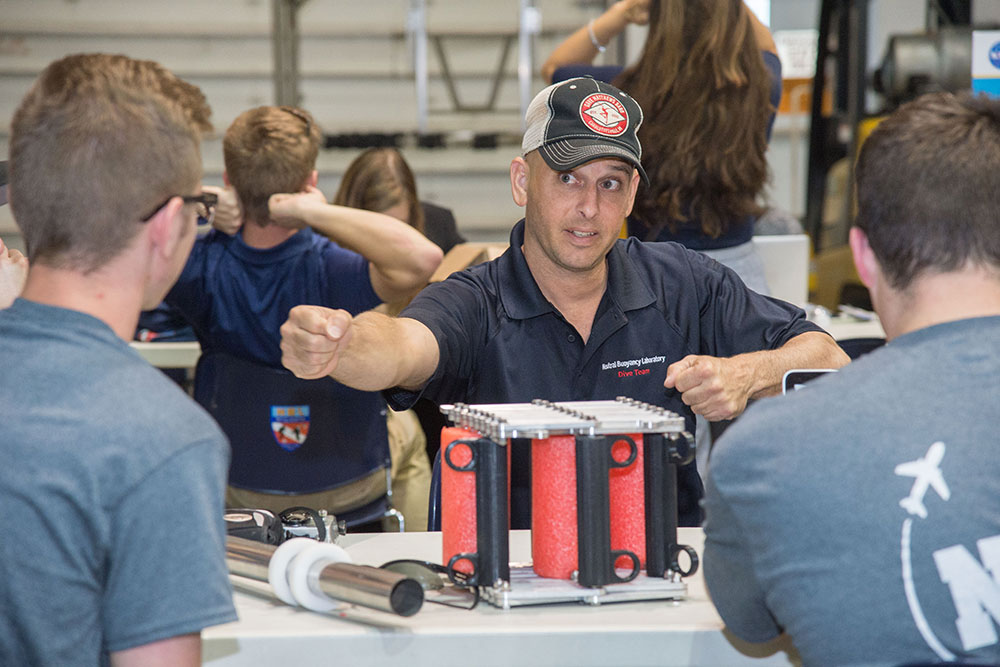 A member of the dive team from the Johnson Space Center's Neutral Buoyancy Laboratory discusses the operation of a gap spanner boom prototype with the designers from UNL's Air and Space Research Team.