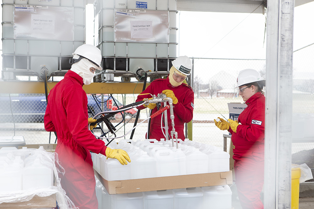Hunter Flodman, Russell Parde and Sarah Herzinger work in the parking lot staging grounds during Monday's hand sanitizer production. (Nebraska Ethanol Board photo)