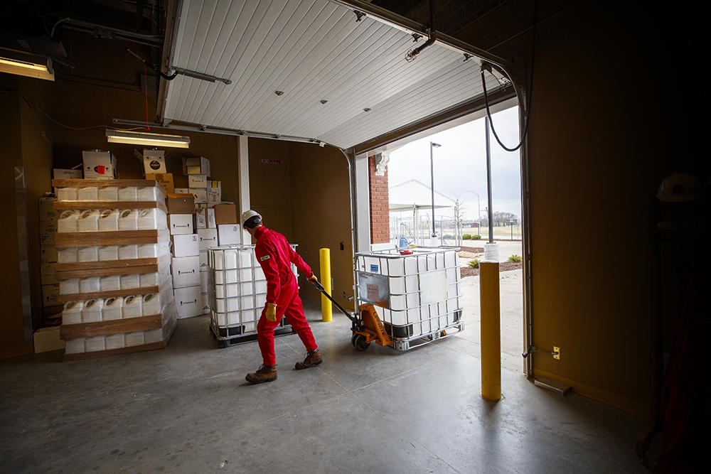 Hunter Flodman, assistant professor of practice in chemical and biomolecular engineering, moves a container of chemicals into the mixing room at Food Innovation Center. (Craig Chandler / University Communication)