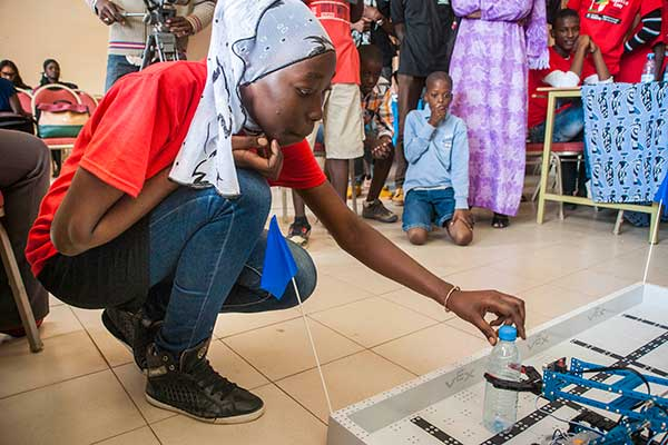 After her team's robot finishes a competition run, a student removes a water bottle from it's claw during the third day of the SenEcole robotics camp in Dakar, Senegal this past March.