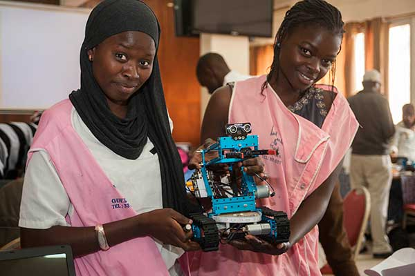 Two female students show off their assembled robot on the first day of the SenEcole robotics camp in Dakar, Senegal, this past March.