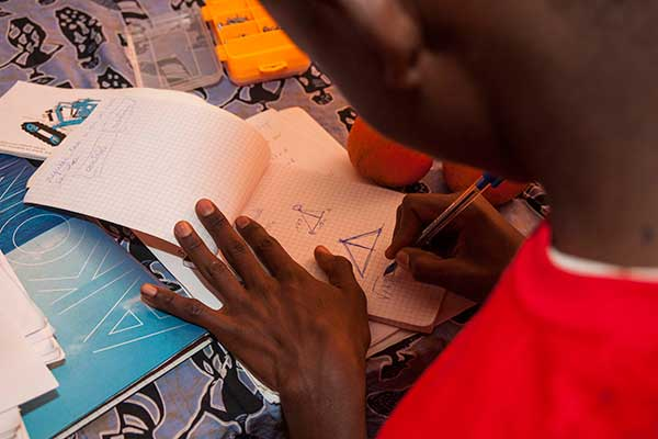 A student sketches out possible changes to his team's robot at the SenEcole robotics camp in Dakar, Senegal this past March.
