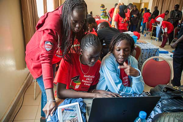 Three students work to finish programming their team's robot during the third day of the SenEcole robotics camp in Dakar, Senegal this past March.