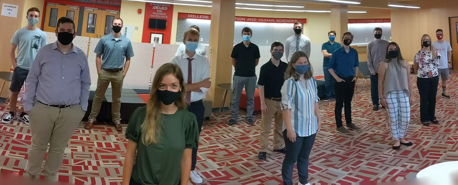 A panoramic image of 16 NTECI cohort students in business casual clothing, standing socially distanced and wearing masks, all looking at the camera.