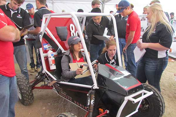 Members of the Husker Racing Baja SAE team discuss their car design with judges during the Baja SAE Collegiate Design Series event in Gorman, California.