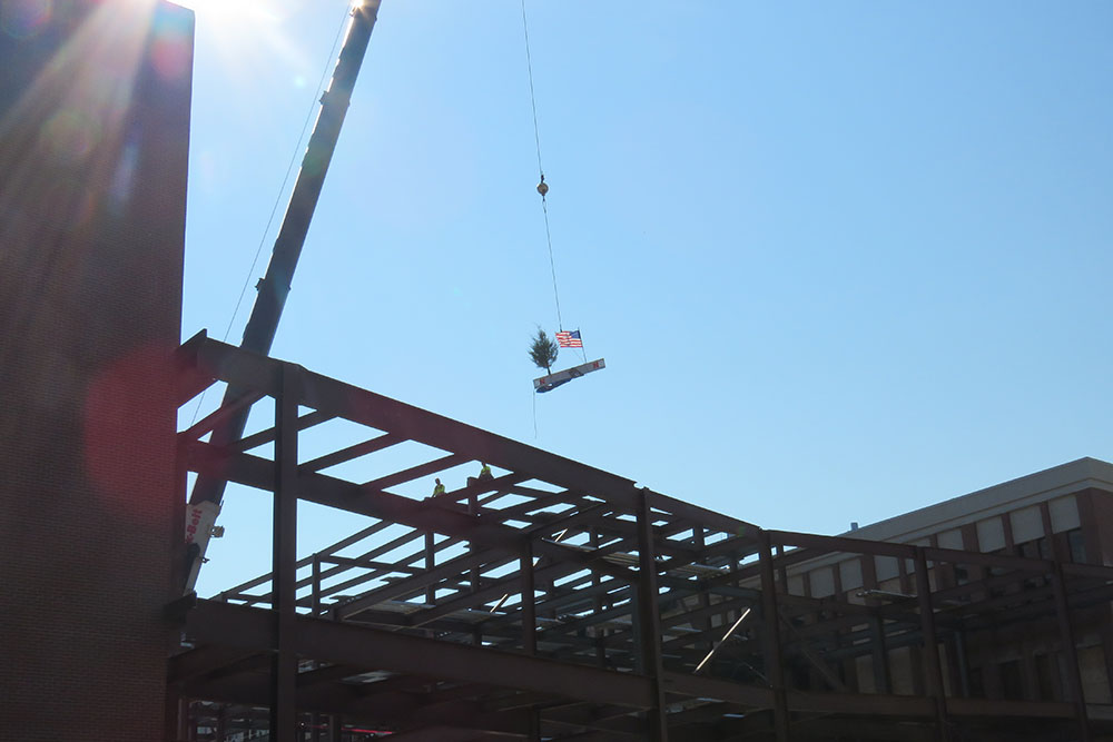 The final steel beam is raised during the Topping Out ceremony for Phase 1 of the college's construction project.
