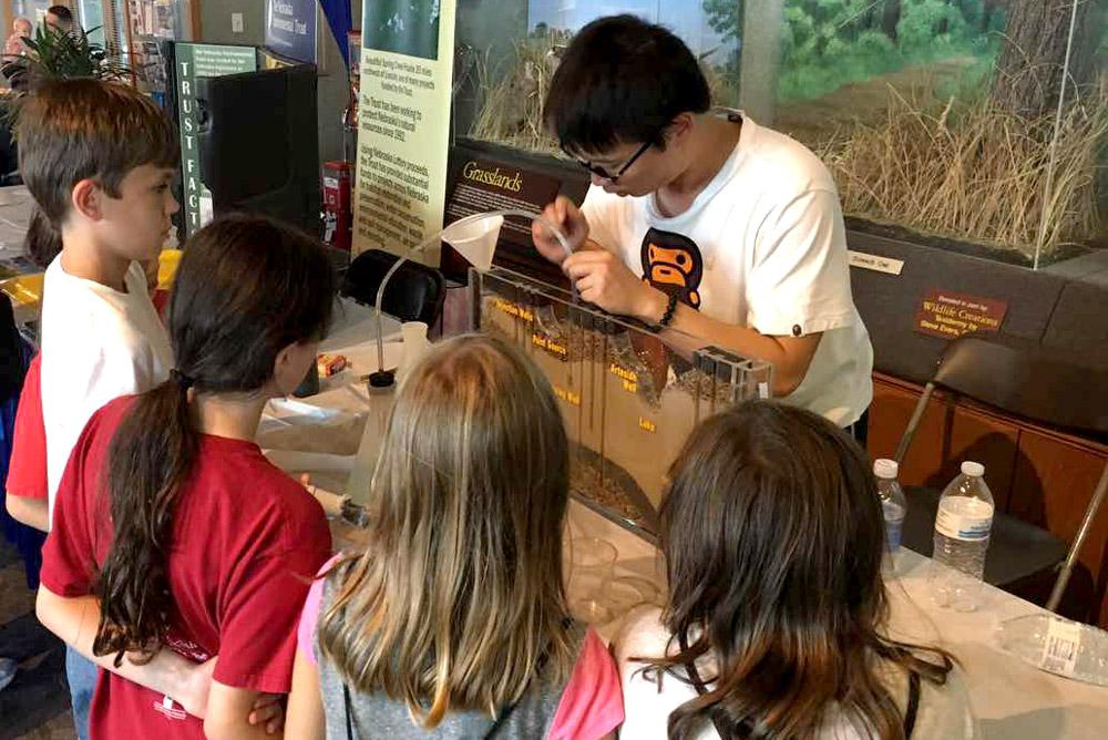 Shaobin Li shows children how pollutants move through soil