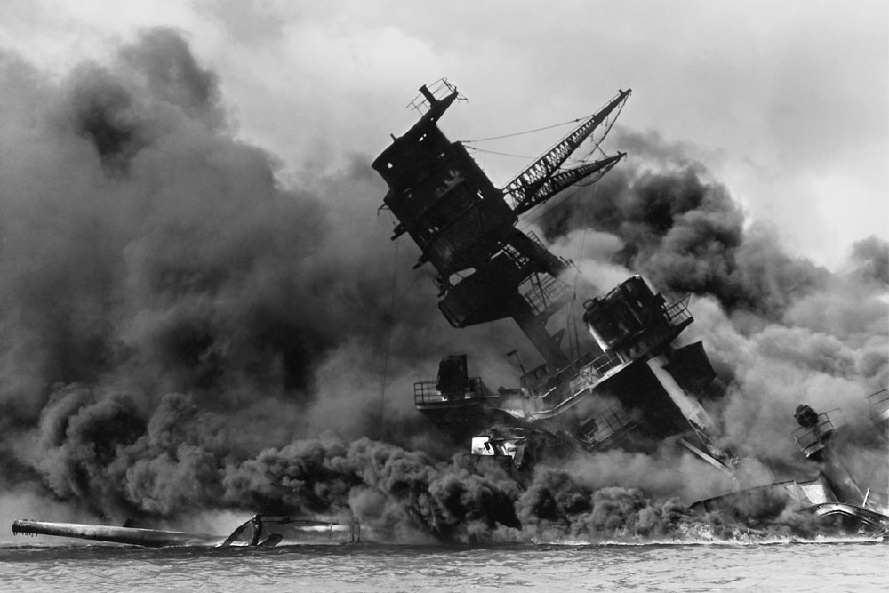 Shortly after being hit by a bomb dropped by a Japanese airplane, the USS Arizona burns in the water off the coast of Pearl Harbor.