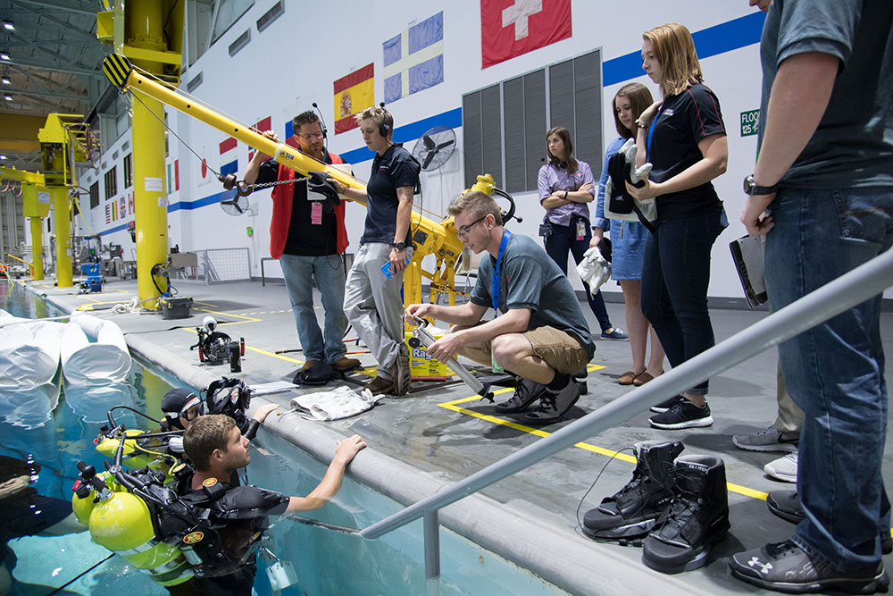 Team leader Nathan Borcyk explains to a NASA diver how to operate the anchoring device during a test in the Johnson Space Center's Neutral Buoyancy Laboratory pool.