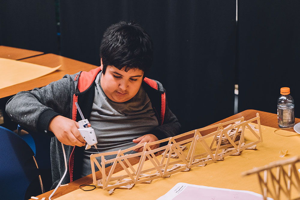 "A student works to construct a bridge during the ""Bridge Busters"" event."