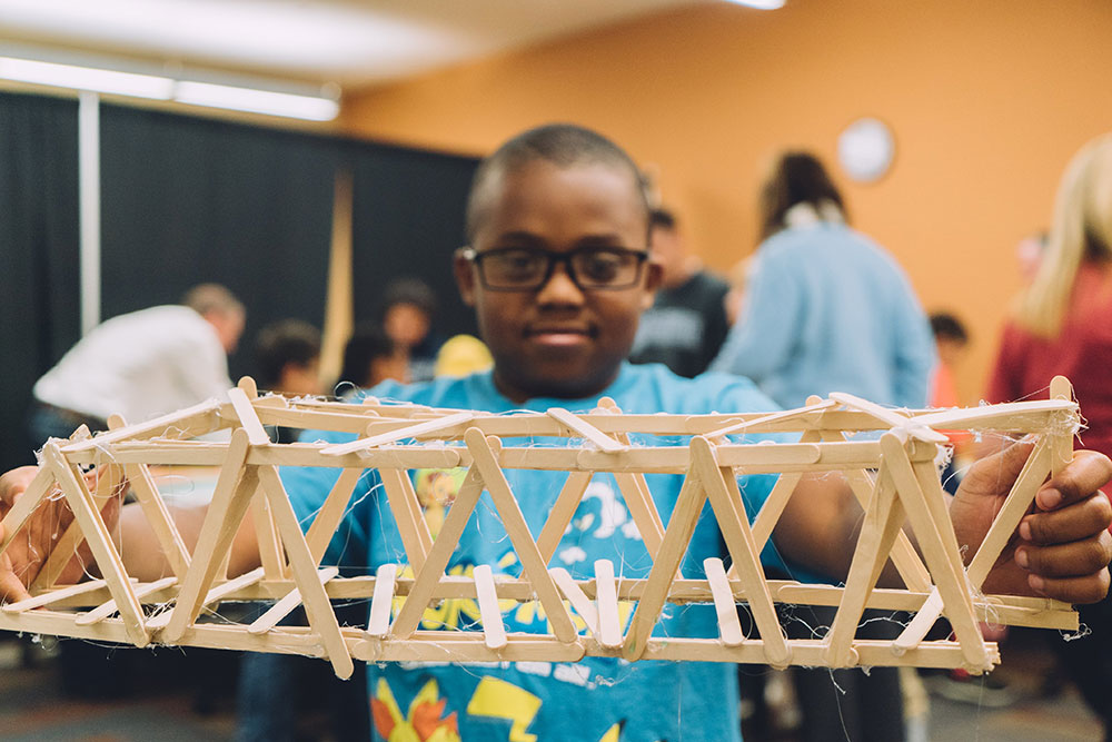 "A student shows off a completed bridge during the ""Bridge Busters"" event."