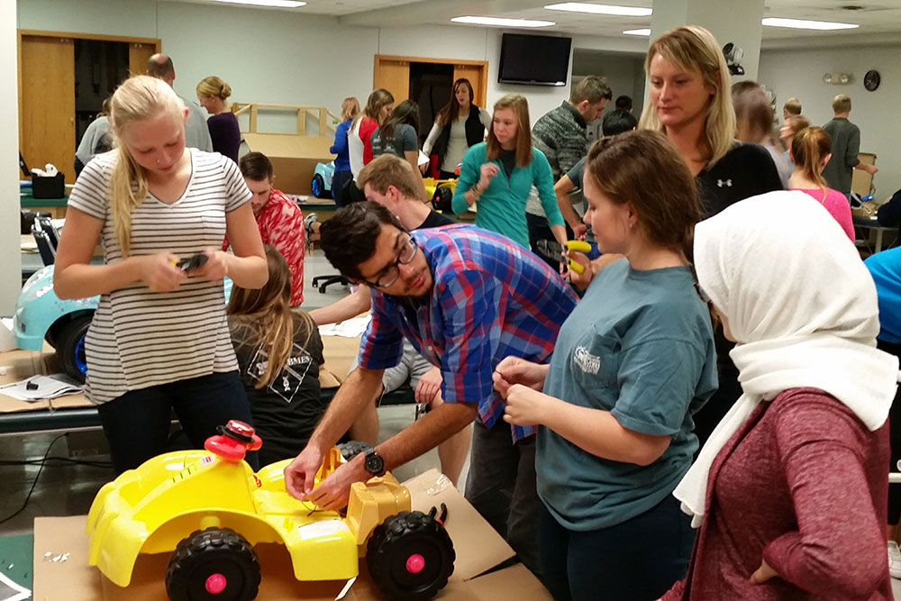 A team of biological systems engineering students works on a car as part of their senior design capstone project. This team is addressing issues to make future Go Baby Go cars easier for the children to operate.