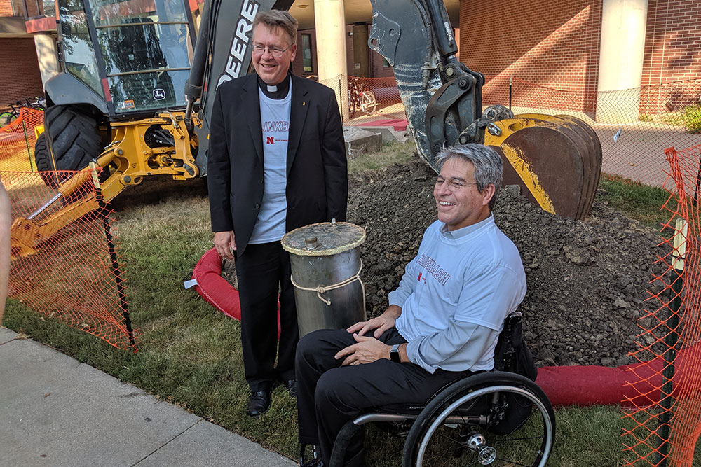 Father Bill Holoubek (left) and College of Engineering Dean Lance C. Pérez spend a moment with the time capsule before it was relocated to a temporary home.