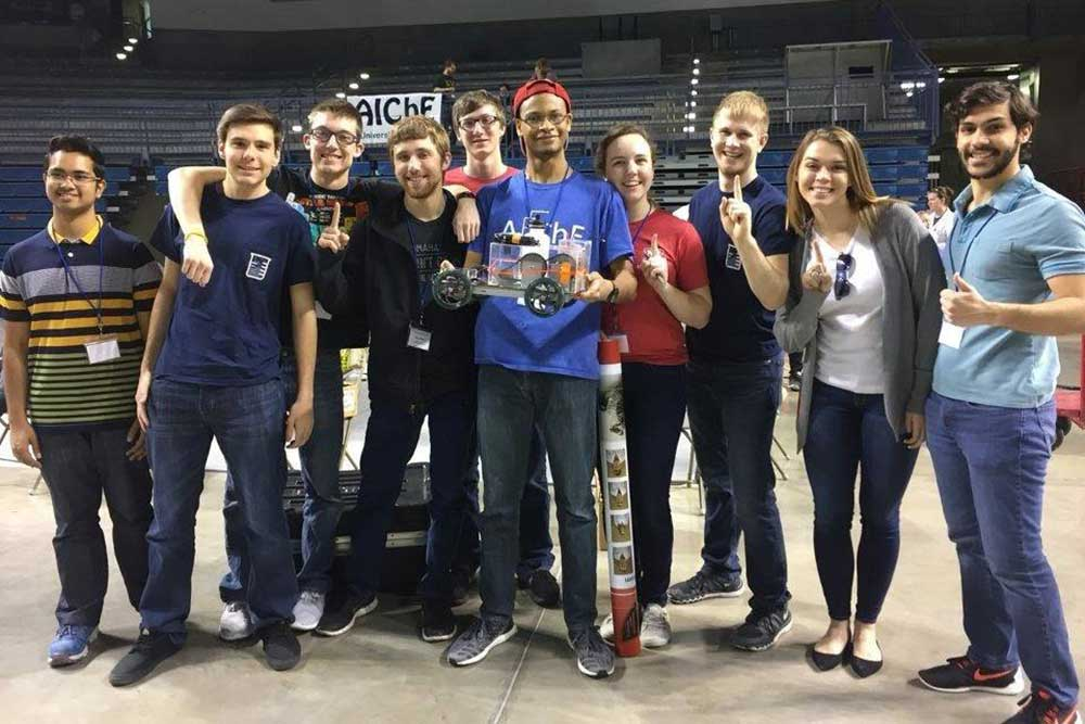 "A team of College of Engineering students – (from left), Ahbab Murtoza, Alex McKinney, Austin Eidem, Bryce Puck, Eric Burbach, Julian Davis, Mary Rethwisch, Austin Osborn, Shelby Williby and Ernesto Bravo Baltodano – and its car, ""Redemption"" took first place in the Chem-E-Car competition at the AIChE Mid-America Student Regional Conference in Tulsa, Oklahoma."