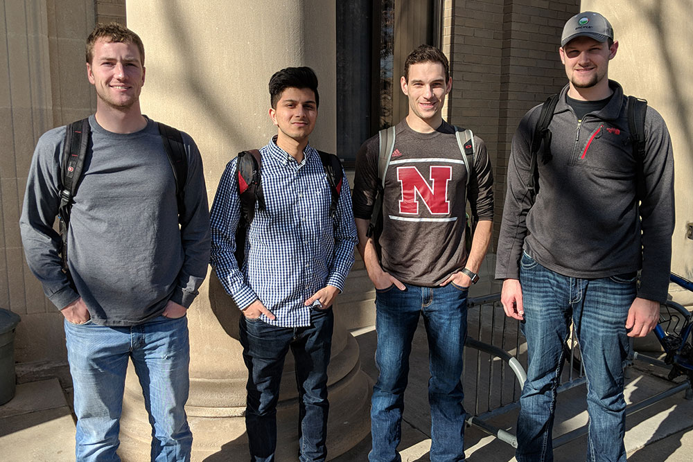 A team of biological systems engineering senior design capstone students (from left) Andrew Minarick, Rohan Sarmah, Steven Cahoy and Nate Meduna have created a creeper device to help a paralyzed mechanic get under vehicles.