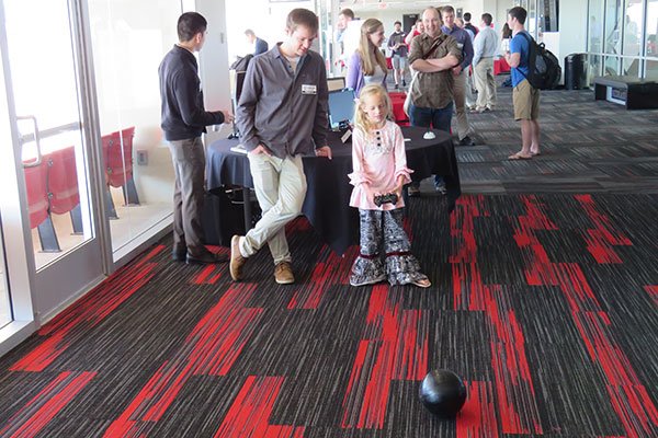 An electrical and computer engineering student helps a young visitor control the 2-1B Spheroid robot at the Senior Design Showcase on April 22 on the East Stadium Club Level of Memorial Stadium.