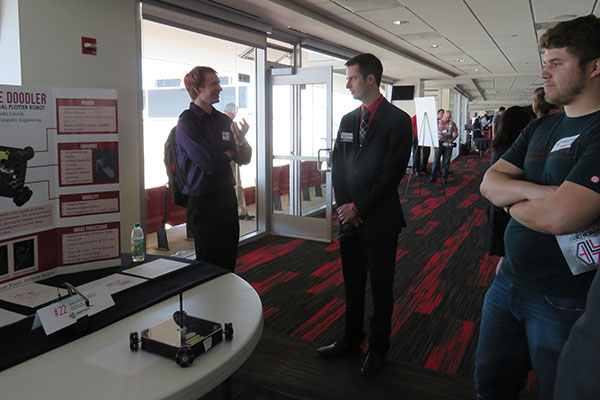 Alex Hinton (center) discusses the Salvadoodle Doodler with visitors to his team's booth at the Senior Design Showcase on April 22 on the East Stadium Club Level of Memorial Stadium.