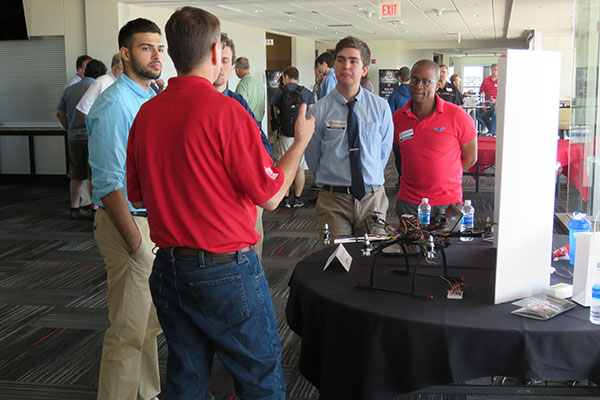 Visitors listen to an explanation of a drone surveillance system developed by electrical and computer engineering students Brandon Guenther, Jack Olson, Joe Gonzalez and Kossivi Agbenohevi.