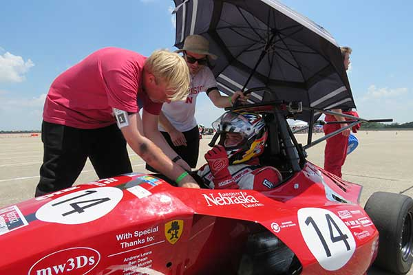 The crew uses an umbrella to keep the driver cool as they work on the Husker Motorsports Formula SAE car before Friday's autocross run at Lincoln Airpark.