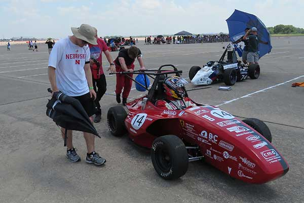 The crew pushes the Husker Motorsports Formula SAE car to the track before Friday's autocross run at Lincoln Airpark.