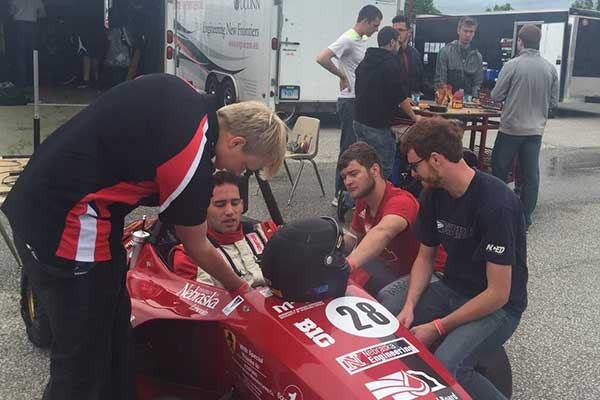 The Husker Motorsports team puts finishing touches on its car before a dynamics event in Barrie, Ontario. After a ninth-place overall finish, the team of UNL engineering students is looking forward to a big finish at this week's event at Lincoln Airpark.
