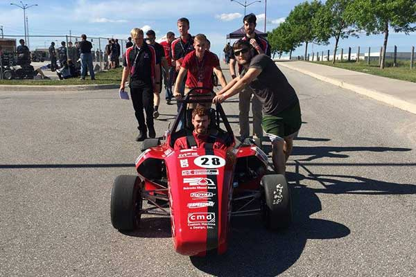The Husker Motorsports team pushes its car to the track in Barrie, Ontario. After a ninth-place overall finish, the team of UNL engineering students is looking forward to a big finish at this week's event at Lincoln Airpark.
