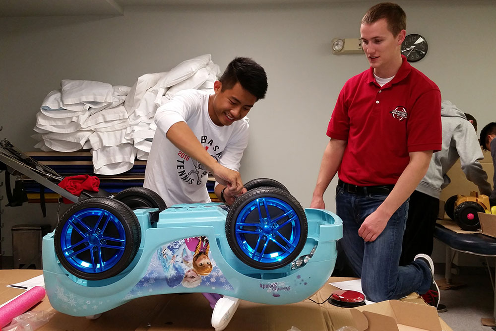 "Two Nebraska Engineering students rewire a ""Frozen""-themed car during at the Go Baby Go build Oct. 15."